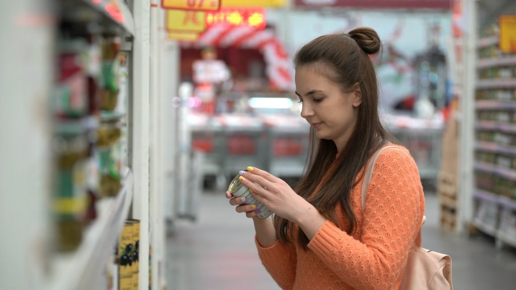 woman buys canned food in supermarket or store